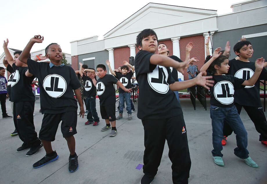 """Alexis Yanez (center) leads the after school group """"Live Loud """" in a performance as the Athlos Leadership Academy and the Pecan Valley Neighborhood Association host a National Night Event at the campus on October 7, 2014. Photo: TOM REEL"""