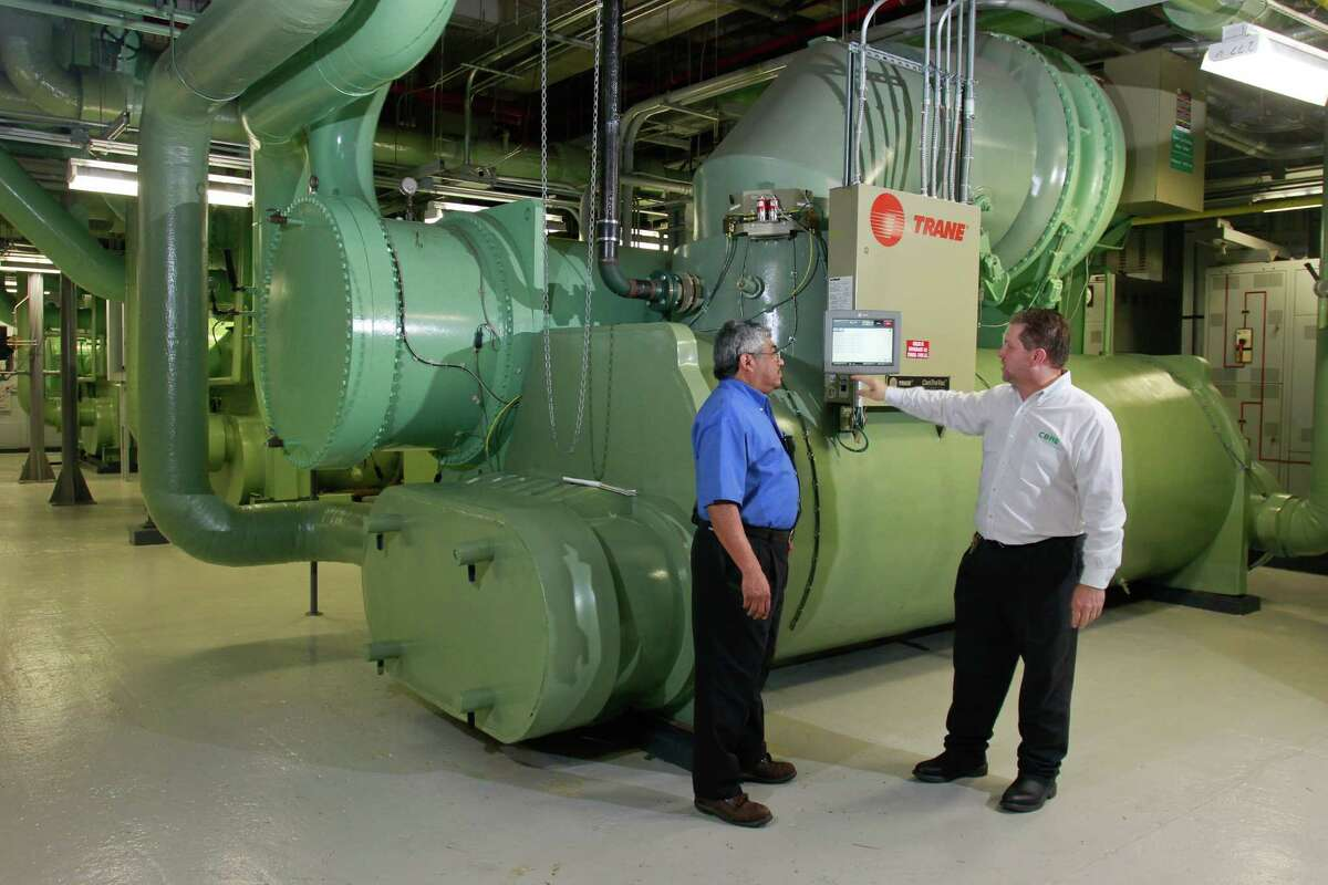 Engineering department building operator Daniel Cisneros, left, and chief operating engineer Kenneth Woods, next to the #3 chiller in the central plant at 2 Houston Center. (For the Chronicle/Gary Fountain, October 6, 2014)