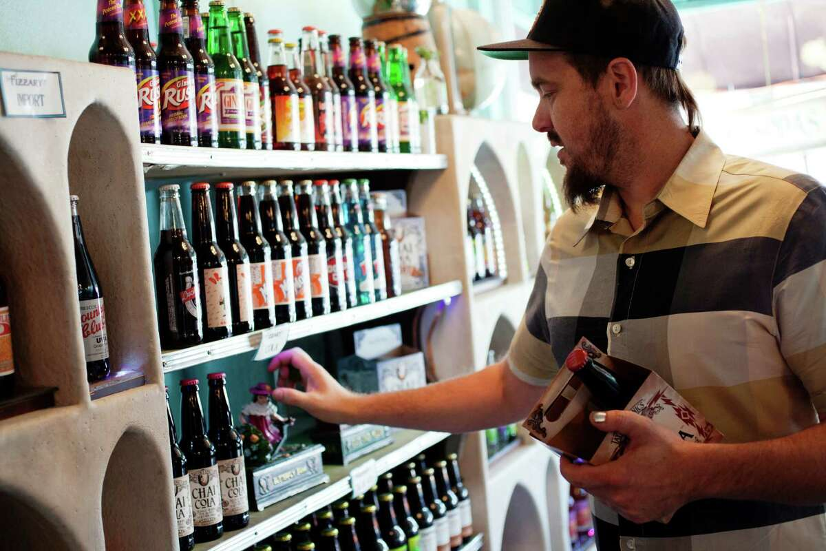 Co-owner Taylor Peck stocks sodas at the Fizzary shop in the Mission District. San Francisco voters are considering an unprecedented 2-cents-per-ounce tax on sugary drinks.