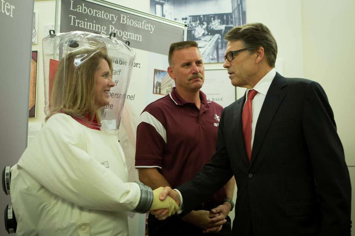 Gov. Perry gets an up-close look at precautions taken at the UTMB laboratory in a gloved greeting by lab manager Terry Juelich, left, and research scientist Curtis Klages during Tuesday's tour.