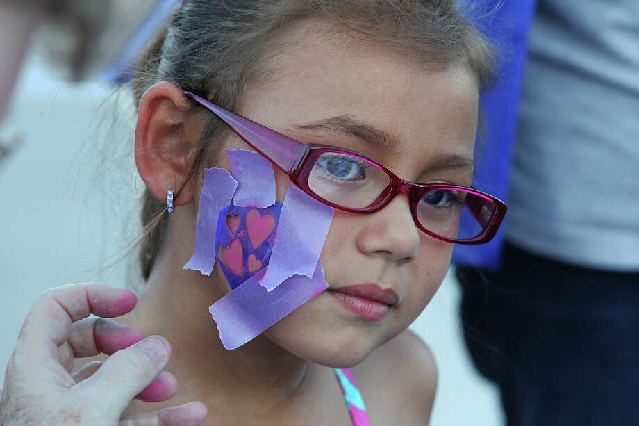First grader Jenna Bostick gets a stencil face painting as the Athlos Leadership Academy and the Pecan Valley Neighborhood Association host a National Night Event at the campus on October 7, 2014. Photo: For The San Antonio Express-News