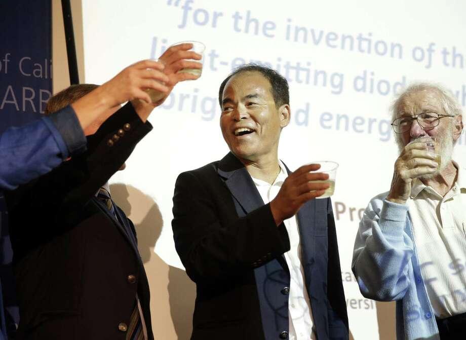 American scientist Shuji Nakamura of the University of California at Santa Barbara celebrates with fellow scholars, including Professor Herbert Kroemer (right), a 2000 physics Nobel winner. Photo: Jae C. Hong / Associated Press / AP
