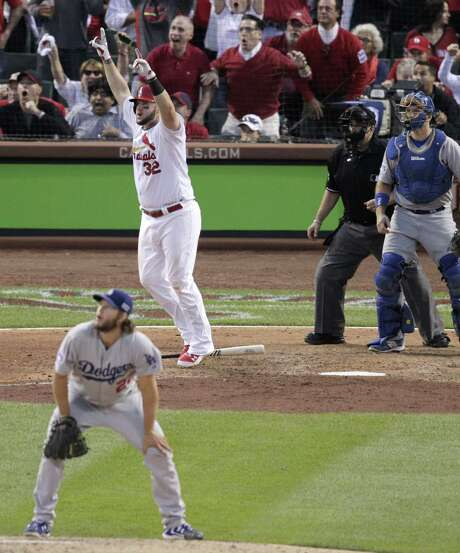 The Cardinals' Matt Adams celebrates after connecting for a three-run homer off Dodgers ace Clayton Kershaw, who watches the ball fly out of Busch Stadium in the seventh inning. Photo: Tom Gannam / Associated Press / FR45452 AP