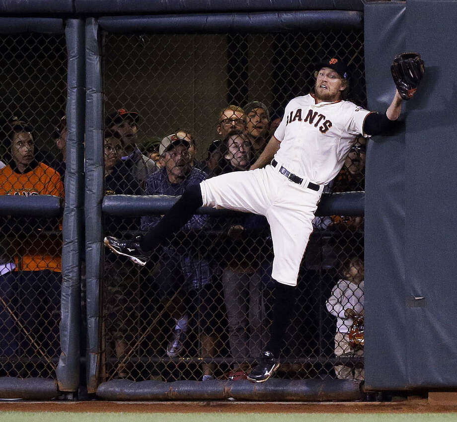The Giants' Hunter Pence makes a difficult catch against the wall in the sixth inning as fans look on during San Francisco's series-clinching victory over the Nationals on Tuesday night at AT&T Park. Photo: Ezra Shaw / Getty Images / 2014 Getty Images