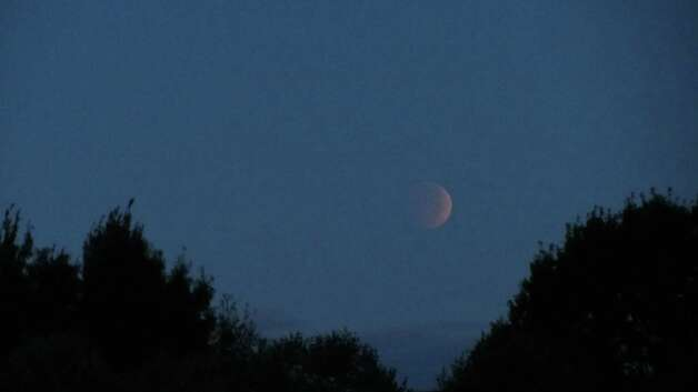 The lunar eclipse can be seen from the Crossings town park in Colonie early Wednesday, Oct. 8, 2014. The photograph was taken just before the moon was fully eclipsed. (Bob Gardinier / Times Union)