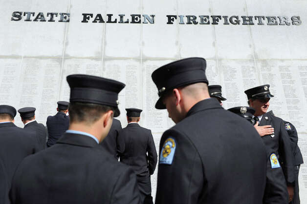 Firefighters gather to pay their respects at the monument following the New York State Fallen Firefighters Memorial Ceremony on Tuesday, Oct. 7, 2014, at the Empire State Plaza in Albany, N.Y. (Cindy Schultz / Times Union) Photo: Cindy Schultz, Albany Times Union / 00028598A