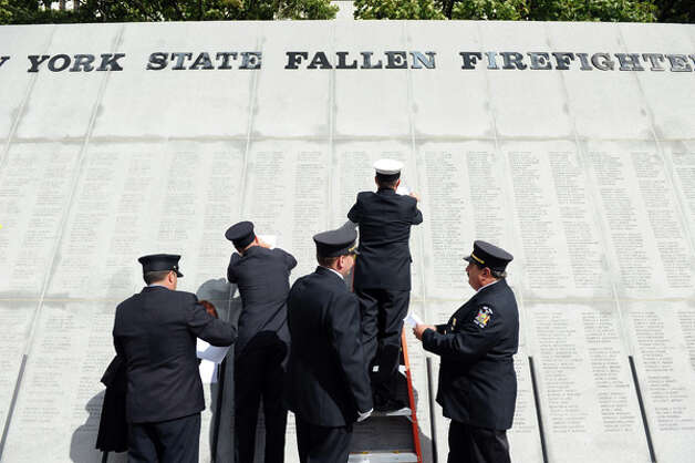 Firefighters trace names engraved in the monument following the New York State Fallen Firefighters Memorial Ceremony on Tuesday, Oct. 7, 2014, at the Empire State Plaza in Albany, N.Y. (Cindy Schultz / Times Union) Photo: Cindy Schultz, Albany Times Union / 00028598A