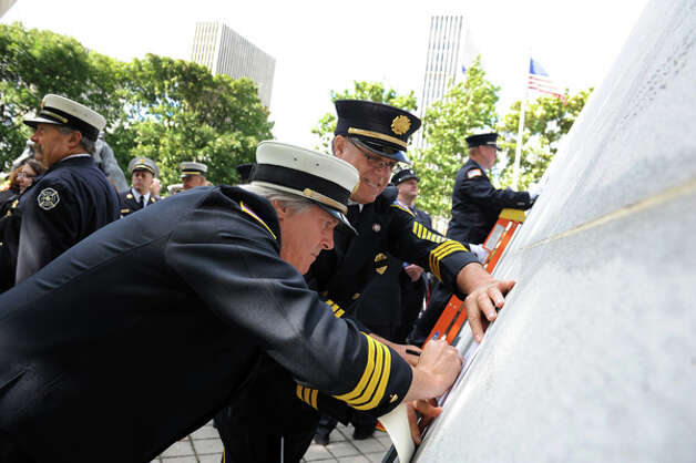 Chief Tim Shone of the Laurelton Fire Dept., center, and Commissioner Paul Groat trace the name of firefighter Arthur Sink following the New York State Fallen Firefighters Memorial Ceremony on Tuesday, Oct. 7, 2014, at the Empire State Plaza in Albany, N.Y. (Cindy Schultz / Times Union) Photo: Cindy Schultz, Albany Times Union / 00028598A
