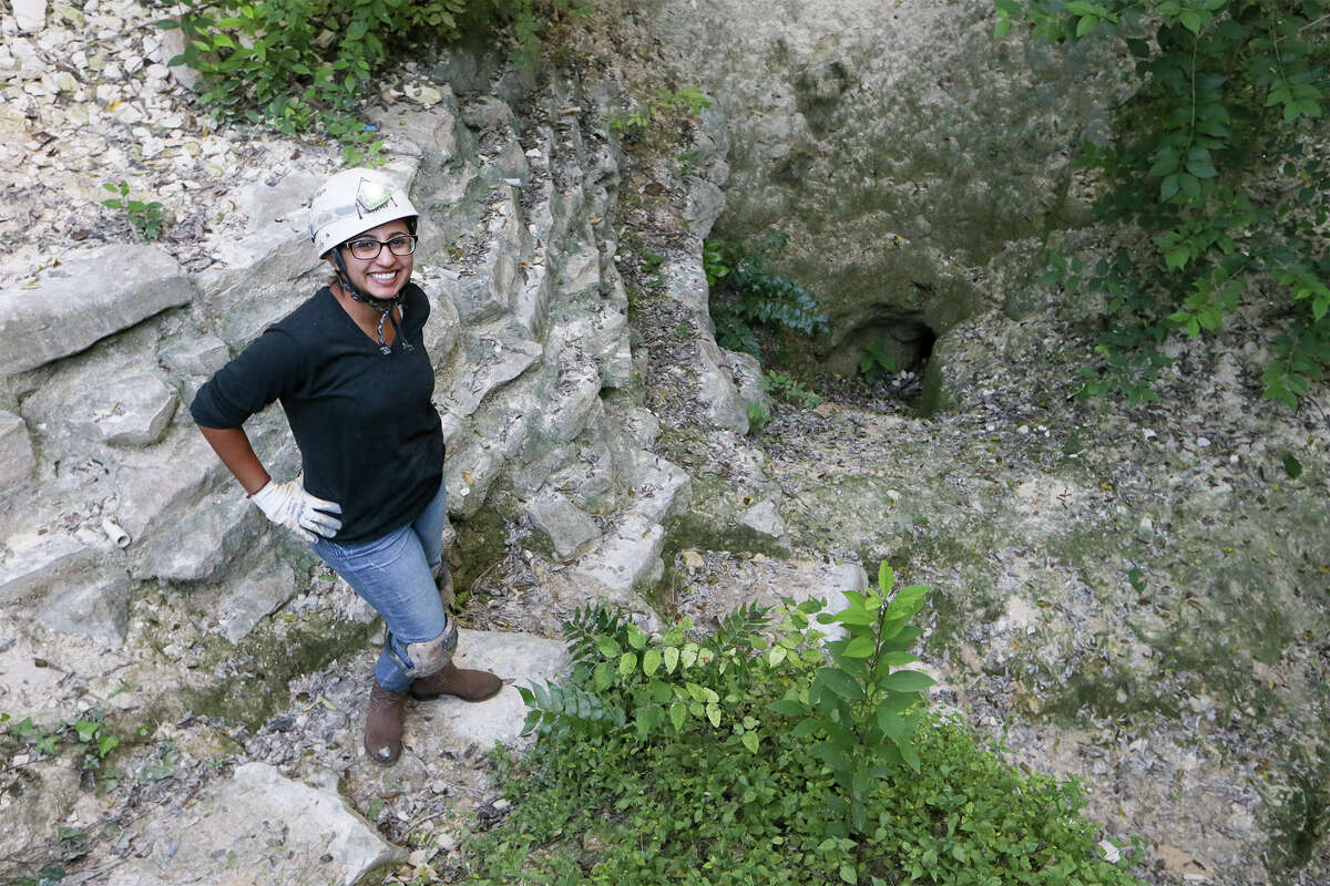 Stephanie Guzman stands above the original entrance to Robber Baron Cave, now closed, on Wednesday, Sept. 24, 2014. Robber Baron Cave, at the corner of Nacogdoches Rd. and Camellia Dr., is the longest and one of the most significant caves in Bexar County with one mile of mapped passage. Photo by Marvin Pfeiffer / EN Communities