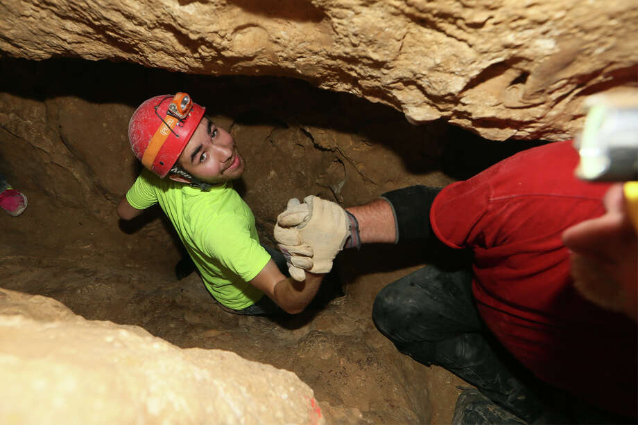 John Delgado (left) drops down a chute with the help of Michael Harris on a tour of Robber Baron Cave on Wednesday, Sept. 24, 2014.  Robber Baron Cave, at the corner of Nacogdoches Rd. and Camellia Dr., is the longest and one of the most significant caves in Bexar County with one mile of mapped passage.  Photo by Marvin Pfeiffer / EN Communities Photo: MARVIN PFEIFFER, Marvin Pfeiffer / EN Communities / EN Communities 2014