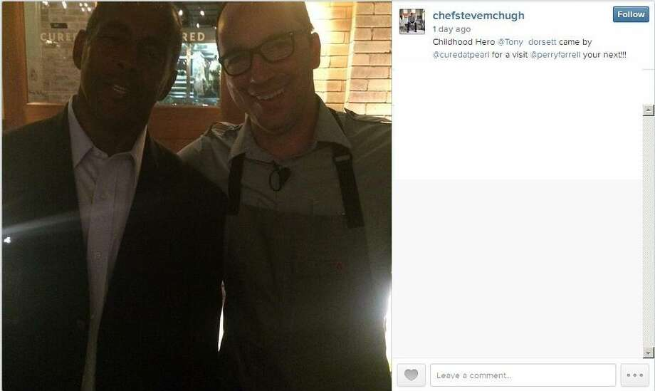 Dallas Cowboys great Tony Dorsett visits Cured in San Antonio and poses with the restaurant's owner Steve McHugh.