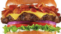 The Mile High Bacon Cheese Thickburger at Carl's Jr. has 1,190 calories. The breakdown:  a ½-pound charbroiled beef patty topped with American cheese, red onion, lettuce, tomato, mayo and 1.5 ounces of bacon on a fresh-baked bun. Fat grams: 80. Sodium: 2,650 mg. Carbs: 60 g. Dietary fiber: 4 g. Protein: 59 g.