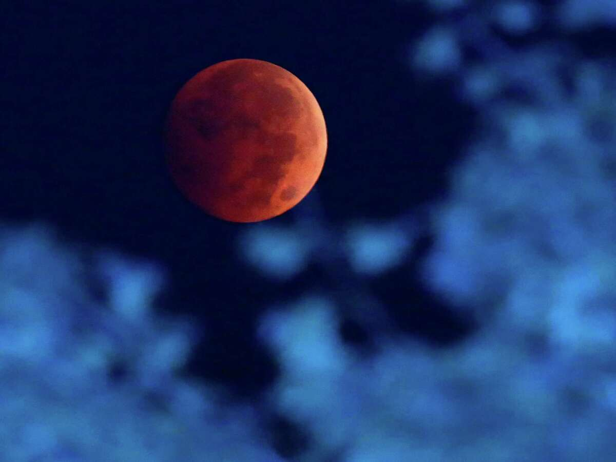 The Earth's shadow is cast over the moon during a total lunar eclipse over Milwaukee on Wednesday, Oct. 8, 2014. The red hue results from sunlight scattering off Earth's atmosphere, in what is known as a