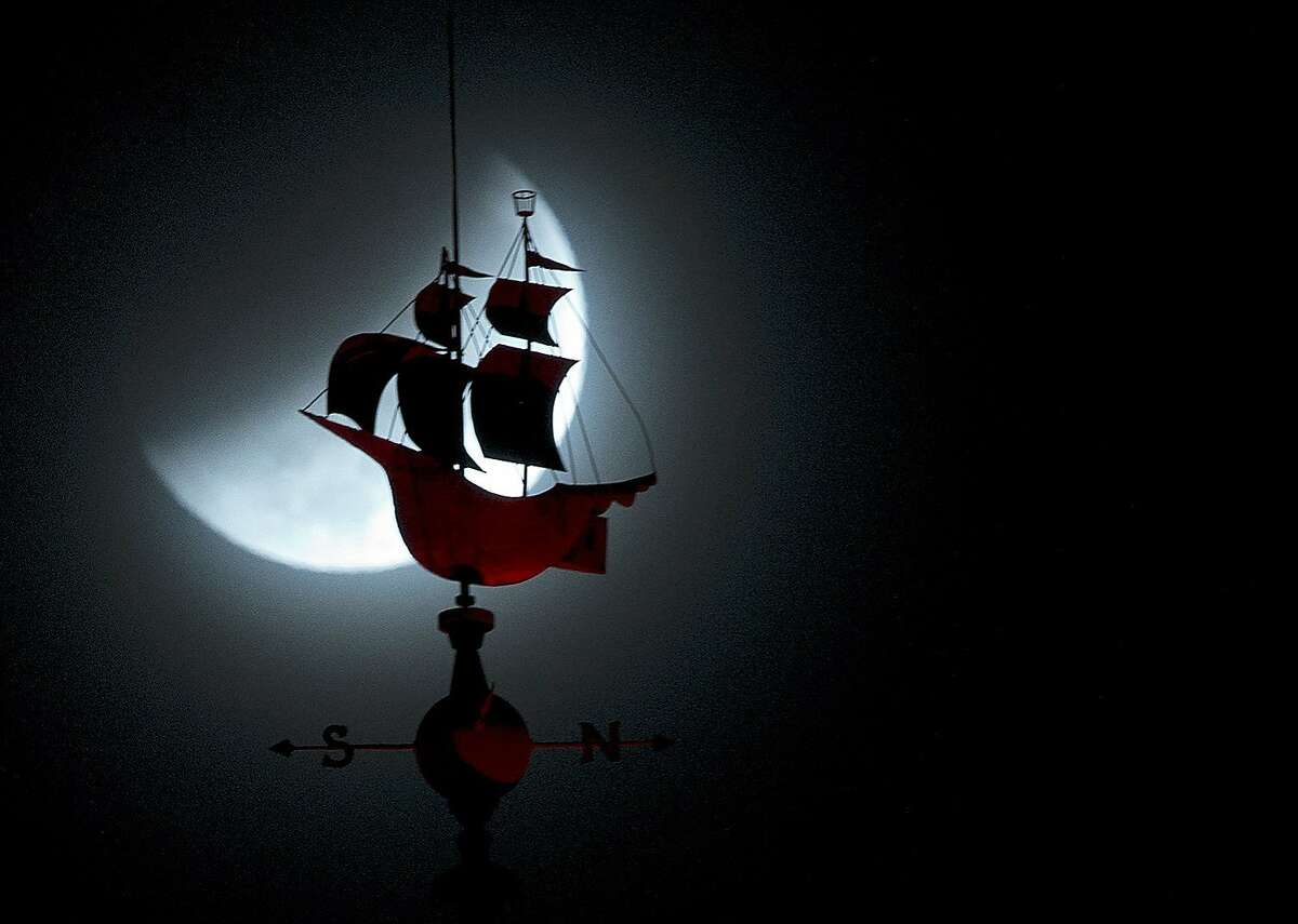 The Earth's shadow begins to fall over the moon during a total lunar eclipse, behind a weathervane shaped like a Spanish galleon on the Freedom Tower in Miami, Wednesday, Oct. 8, 2014.
