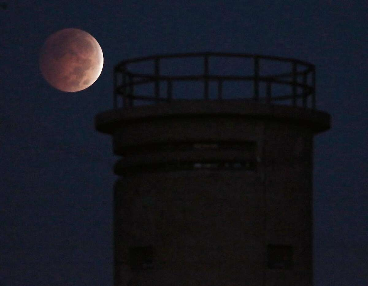 The eclipse of the moon nears totality around 6:30 a.m. EDT as it sets behind the fire tower along Sunset Boulevard near Sunset Beach in Lower Township, N.J., Wednesday, Oct. 8, 2014. A total eclipse of the moon could be seen in Southern New Jersey in the early morning hours before sunrise,