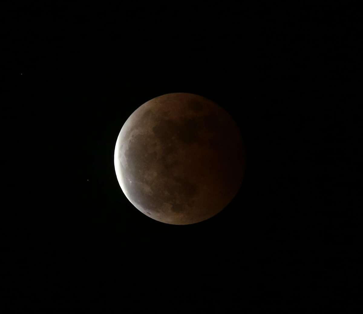 The deep orange color of the moon slowly fades during a Total Lunar Eclipse which is seen Wednesday, Oct. 8, 2014 from Bicutan, Paranaque city, east of Manila, Philippines. Wednesday's eclipse was the second in a series of four total lunar eclipses that occur in six-month intervals and known as a