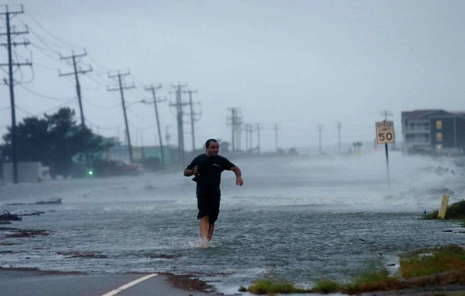 FILE - In this July 4, 2014 file photo, a man crosses a flooded Highway 64 as wind pushes water over the road as Hurricane Arthur passes through Nags Head, N.C. This year's Atlantic hurricane season has so far had the fewest number of storms since 1983, with only five named storms forming so far in the region: Arthur, Bertha, Cristobal, Dolly and Edouard. (AP Photo/Gerry Broome, File) Photo: Gerry Broome, STF / AP