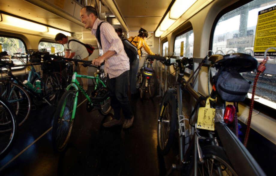 Scott Sugiura looks for a spot to park his bike on a southbound Caltrain. Photo: Liz Hafalia / The Chronicle / SFC