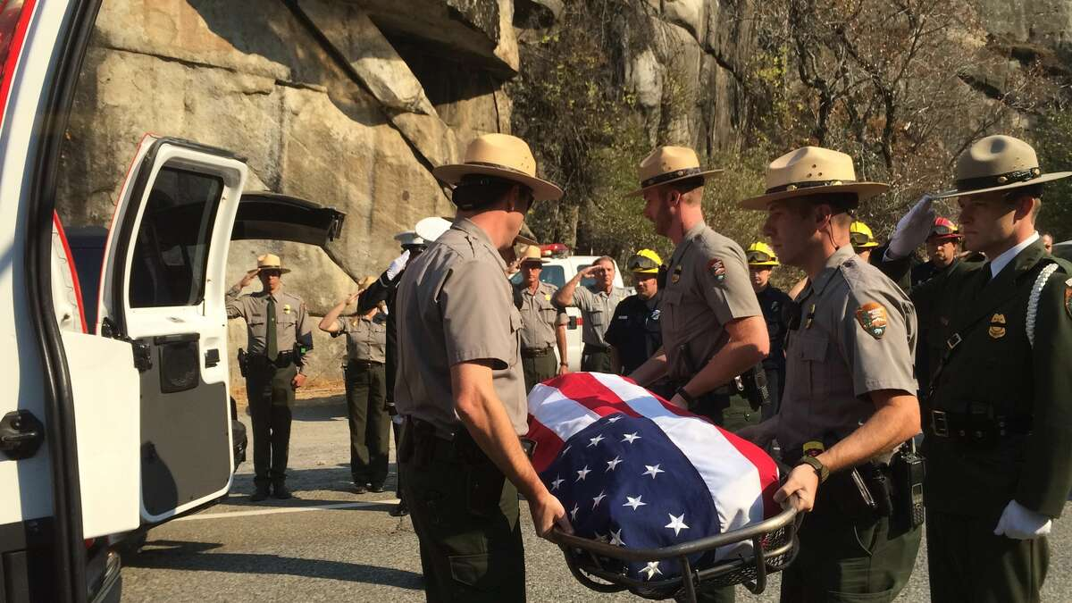 National Park Service rangers Wednesday carry the body of the pilot whose plane crashed in Yosemite as he helped battle a wildfire.