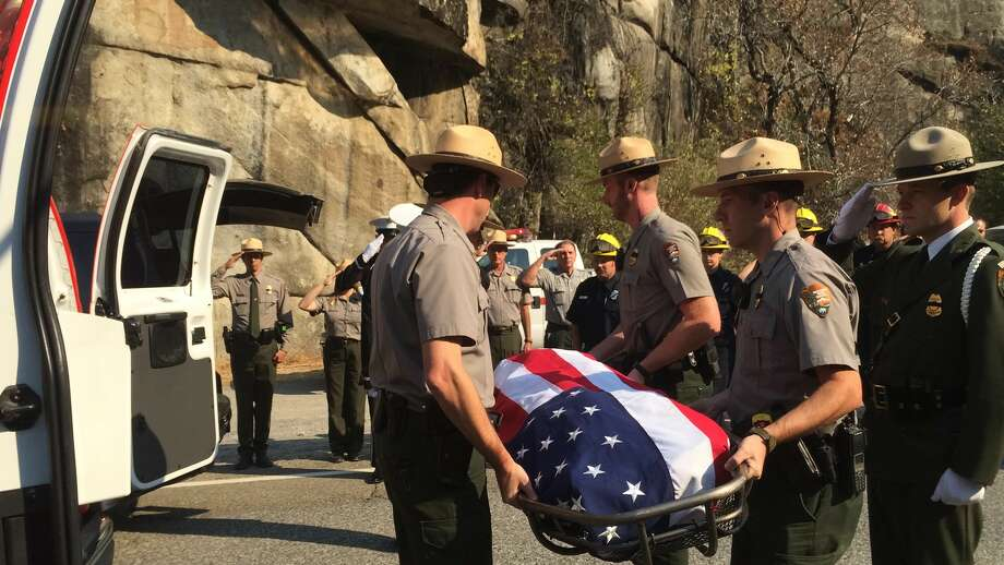 National Park Service rangers Wednesday carry the body of the pilot whose plane crashed in Yosemite as he helped battle a wildfire. Photo: Vivian Ho / Vivian Ho / ONLINE_YES
