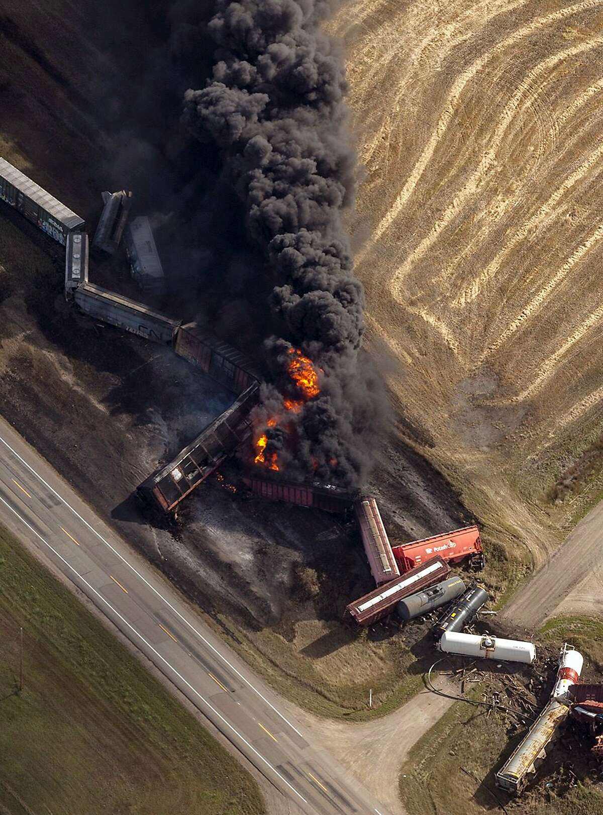 In this aerial photo, a Canadian National Railway Company freight train carrying dangerous goods, derailed and caught fire, burns near the town of Wadena, Saskatchewan, Tuesday, Oct. 7, 2014. The Saskatchewan government said the derailment happened near the small community of Clair, about 13 miles west of Wadena, which is being evacuated. (AP Photo/The Canadian Press, Liam Richards)