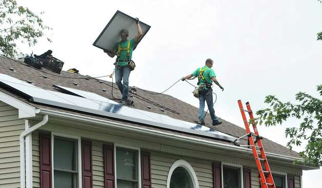 SolarCity installers Zack Bleau, left, and Steve Gowie II,  put in a solar system on the roof of a home on Thursday, Oct. 2, 2014, in Schenectady, N.Y.  In total 41 panels were being installed on the home.   (Paul Buckowski / Times Union) Photo: Paul Buckowski / 00028865A
