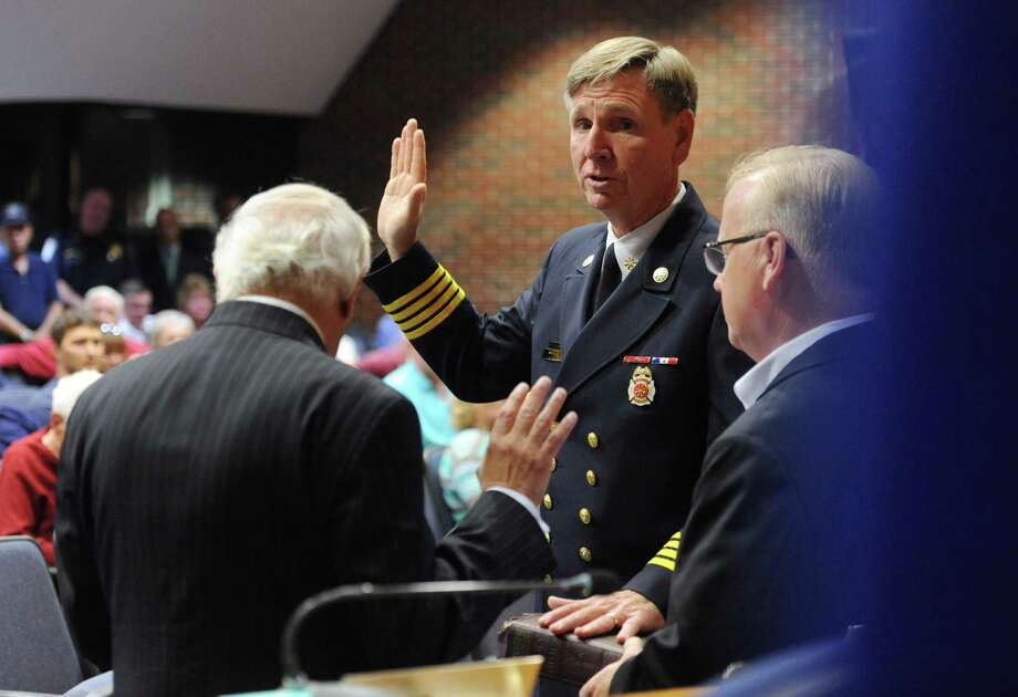 T.J. Wiedl is sworn in as new fire chief at the Town Hall Council Chambers in Danbury, Conn. Wednesday, Oct. 8, 2014.  Former Assistant Fire Chief T.J. Wiedl was promoted to Fire Chief and former Training Officer Mark Omasta was promoted to Assistant Fire Chief in front of a large, enthusiastic crowd at Danbury Town Hall. Photo: Tyler Sizemore / The News-Times