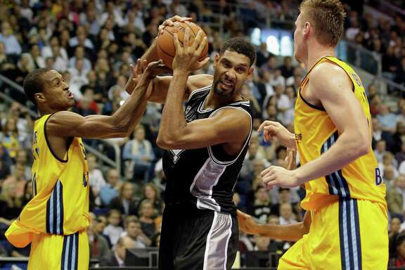 San Antonio Spurs' Tim Duncan, center, and ALBA's Alex Renfroe from the US, left, and Leon Radosevic from Kroatien, right, challenge for the ball during an NBA Global Games basketball match between US team San Antonio Spurs and German team ALBA Berlin in Berlin, Germany, Wednesday, Oct. 8, 2014. (AP Photo/Michael Sohn)