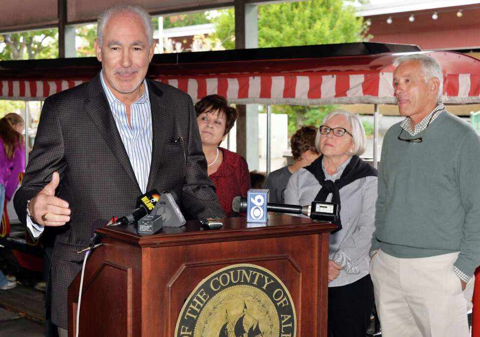 Jeffrey Sperber, left, of Huck Finn's Warehouse announces the move of Hoffman's Playland to property adjacent to Huck Finn's in Albany during a news conference Wednesday Oct. 8, 2014, in Colonie, NY. At right are Playland owners David and Ruth Hoffman. (John Carl D'Annibale / Times Union)