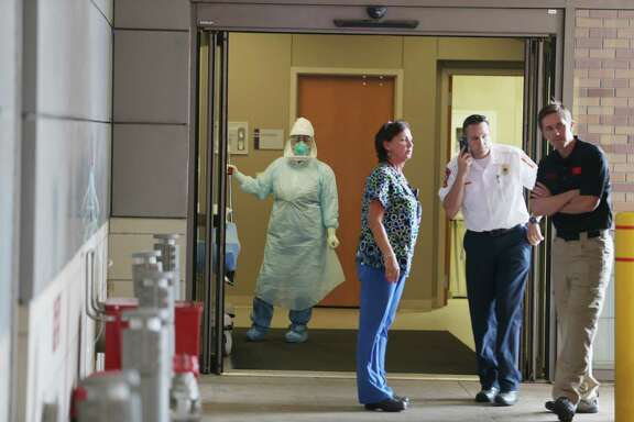 DALLAS, TX - OCTOBER 08:  Health care workers wait for the arrival of a possible Ebola patient at the Texas Health Presbyterian Hospital on October 8, 2014 in Dallas, Texas. Thomas Eric Duncan, the first confirmed Ebola virus patient in the U.S., died earlier today.