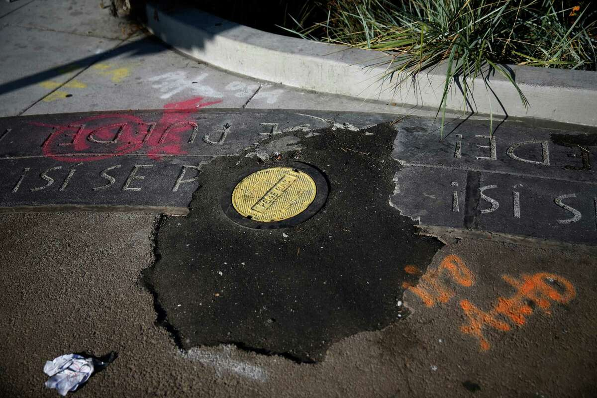 A whole filled with asphalt is seen in newly installed paving in a plaza at Mission Street and Cesar Chavez Street on Oct. 8 in San Francisco.