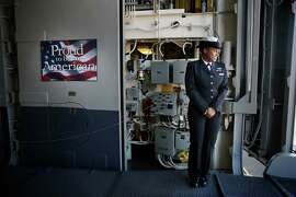 Fabiola Cesar, working as a Messenger of the Watch,  stands at the ships entrance for the arrival of people taking a pubic tour aboard the amphibious assault ship USS America shortly before the start of the tour at Pier 30/32 on Wednesday, October 8,  2014 in San Francisco, Calif.