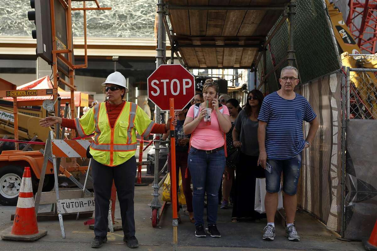 Pedestrians wait to cross O'Farrell Street in San Francisco, Calif. on Thursday, October 2, 2014 during construction related to the Central Subway project.