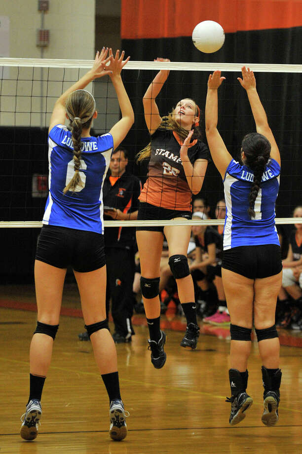 Stamford's Cali Schenkel attempts to spike the ball through Fairfield Ludlowe's April Cooke, left, and Andrea Alvarez during their volleyball match at Stamford High School in Stamford, Conn., on Wednesday, Oct. 8, 2014. Stamford won, 3-2. Photo: Jason Rearick / Stamford Advocate