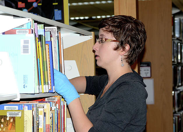 "Emma Spalti, a representative from state Sen. Cecilia Tkaczyk's office, helps dust shelves at the Guilderland Public Library during ""Neighbors Helping Neighbors Day"" on Sept. 26, 2014. (Paulette Doudoukjian)"