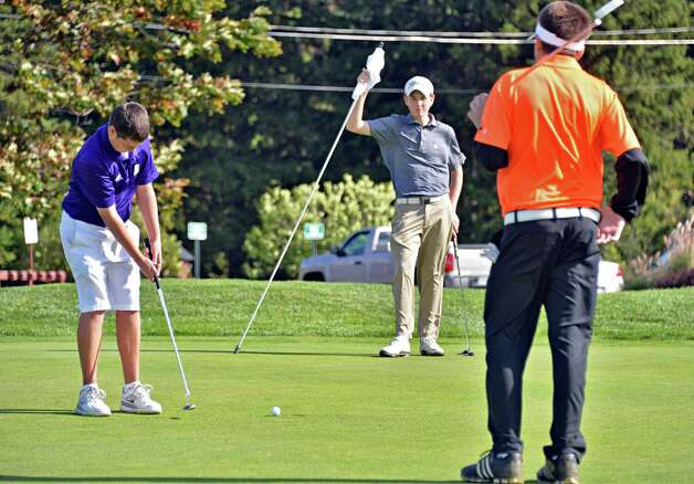 CBA's Connor Adams, left, putts as Albany Academy's Sean Puleo and Bethlehem's Austen Fox, right, look on during the Section II golf Class A championship at the Ballston Spa Country Club Wednesday Oct. 8, 2014, in Ballston Spa, NY.  (John Carl D'Annibale / Times Union) Photo: John Carl D'Annibale / 10028920A