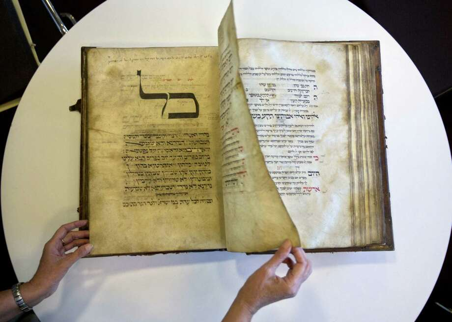 An official at Israel's National Library shows a 13th-century German prayer book containing the first written evidence of the Yiddish language. Photo: Sebastian Scheiner / Associated Press / AP