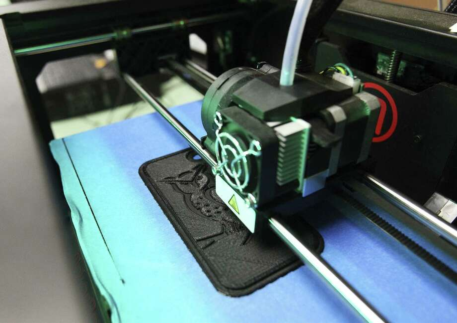A 3-D printer churns out a smartphone case at Highlands High School. Architecture students are trying to raise money for a trip to New York. Photo: Kin Man Hui / San Antonio Express-News / ©2014 San Antonio Express-News