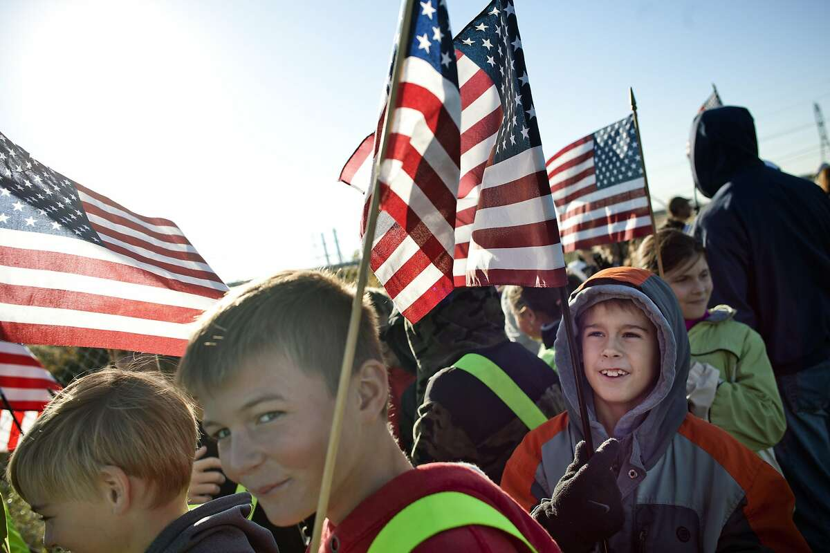 Pine River Elementary fifth-grade student Josh Laieus, 10, holds an American flag as he walks to school as part of International Walk to School Day Wednesday, Oct. 8, 2014 in China Township, Mich. (AP Photo/The Port Huron Times Herald, Jeffrey M Smith) NO SALES