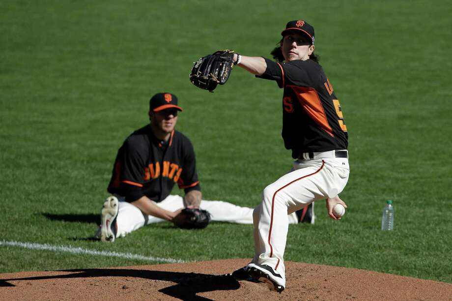 As Jake Peavy watches, Tim Lincecum works to stay sharp during a bullpen session Wednesday. Lincecum has not pitched in the 2014 playoffs and last appeared in a game Sept. 28. Photo: Jeff Chiu / Associated Press / AP