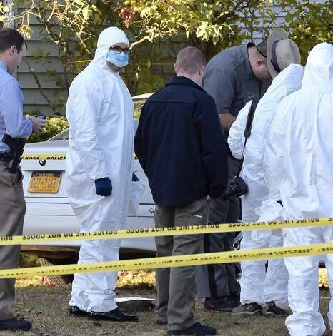 Albany County District Attorney David Soares, second from left, prepares to enter 1846 Western Ave., Guilderland, with police and other prosecutors as they prepare to examine the scene where four people were found dead on Wednesday. (Skip Dickstein / Times Union)