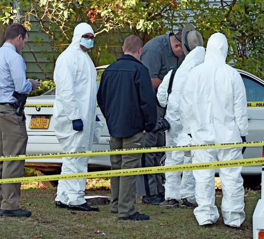 Albany County District Attorney David Soares, second from left, donned overalls to enter the scene of a quadruple homicide at 1846 Western Avenue early Thursday morning Oct. 9, 2014 in Guilderland, N.Y.     (Skip Dickstein/Times Union) Photo: SKIP DICKSTEIN / 10028967A