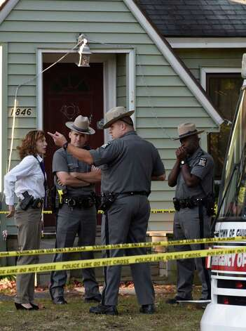 New York State Police BCI investigator speaks with troopers at the scene of a quadruple homicide at 1846 Western Avenue early Thursday morning Oct. 9, 2014 in Guilderland, N.Y.     (Skip Dickstein/Times Union) Photo: SKIP DICKSTEIN / 10028967A