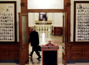A lawmaker leaves the Texas House of Representatives after they passes a final transportation funding bill and adjourned, Monday, Aug. 5, 2013, in Austin , Texas.  The Texas House has passed a bill and the proposed constitutional amendment that would boost spending for roads and bridges. (AP Photo/Eric Gay)