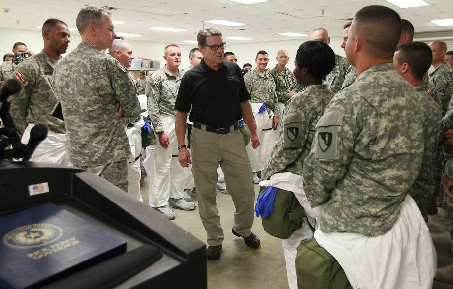 Texas Gov. Rick Perry meet with soldiers from the 36th Engineer Brigade at Fort Hood as they train on how to put on and wear protective clothing and gloves on Thursday, Oct. 9, 2014. The brigade is set to deploy to Liberia as part of Operation United Assistance where they will be building temporary medical facilities in helping the country fight the Ebola virus outbreak. The 450 soldiers from the brigade will be amongst the first to be deployed from Fort Hood to Liberia. Photo: Kin Man Hui, San Antonio Express-News / ©2014 San Antonio Express-News