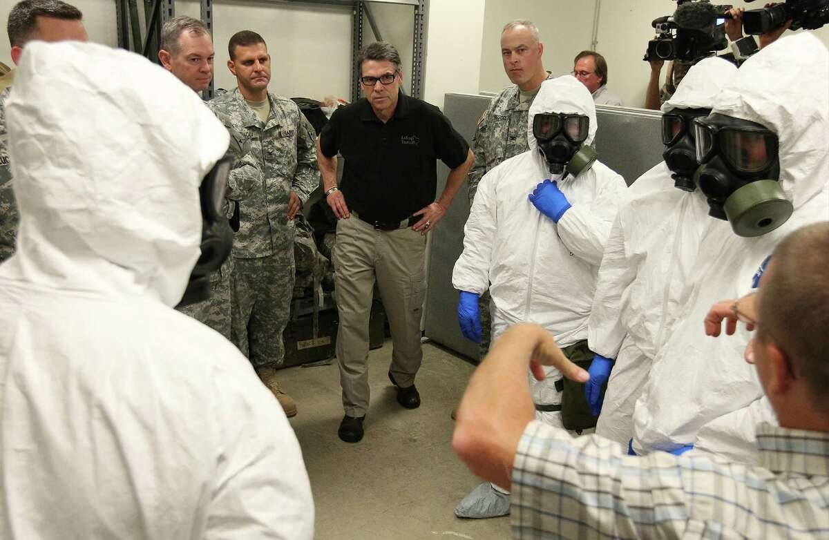 Texas Gov. Rick Perry (center) observe a training session of the 36th Engineer Brigade as they train on how to put on and wear protective clothing and gloves on Thursday, Oct. 9, 2014. The brigade is set to deploy to Liberia as part of Operation United Assistance where they will be building temporary medical facilities in helping the country fight the Ebola virus outbreak. The 450 soldiers from the brigade will be amongst the first to be deployed from Fort Hood to Liberia.