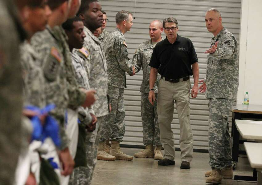 Texas Gov. Rick Perry (center) escorted by Col. Heath Roscoe (right) of the 36th Engineer Brigade meet with soldiers at Fort Hood as they train on how to put on and wear protective clothing and gloves on Thursday, Oct. 9, 2014. The brigade is set to deploy to Liberia as part of Operation United Assistance where they will be building temporary medical facilities in helping the country fight the Ebola virus outbreak. The 450 soldiers from the brigade will be amongst the first to be deployed from Fort Hood to Liberia.