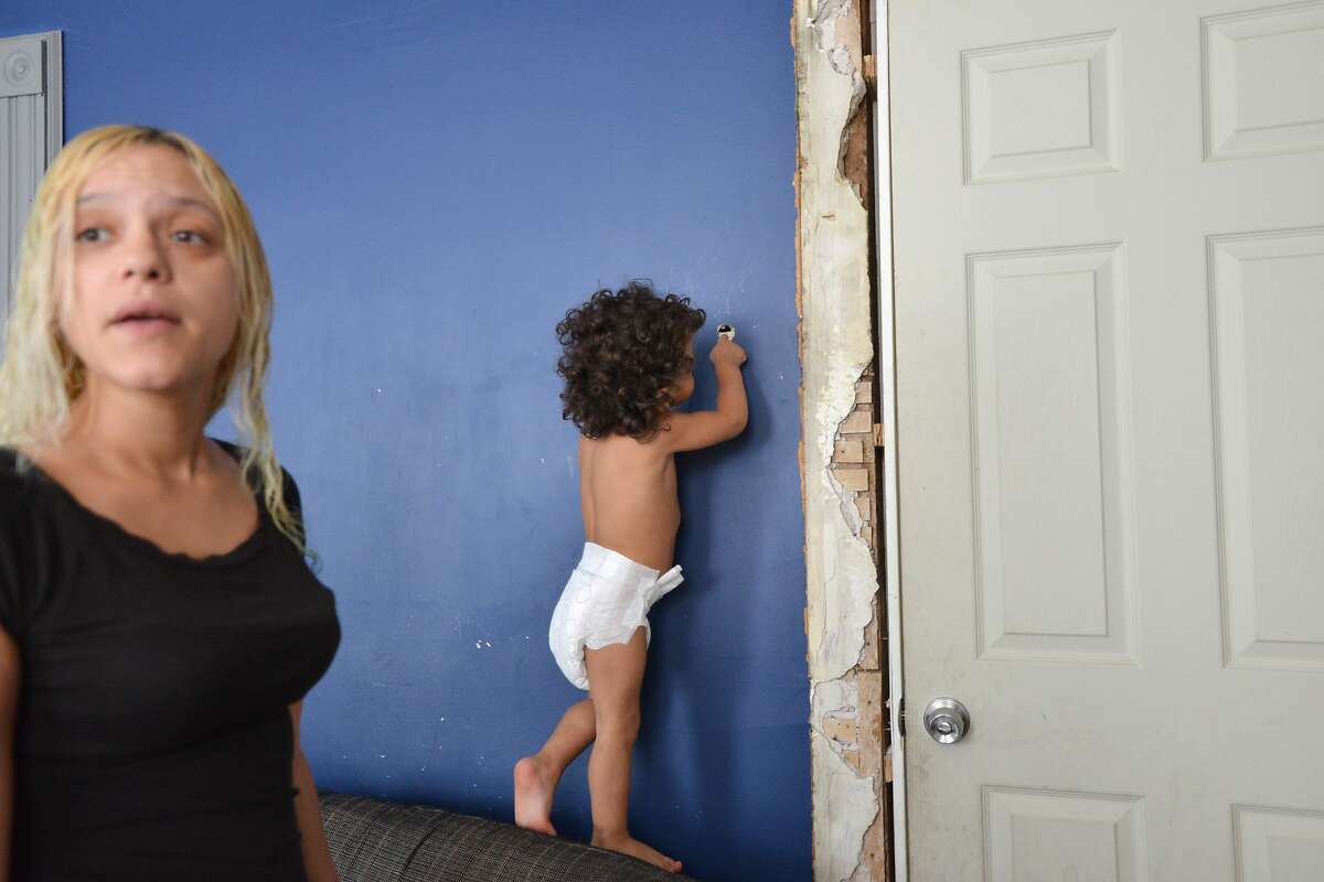 BULLETS THROUGH THE WALLS: Alex Vazquez, 2, looks at a bullet hole as his mother, Melissa, talks about a shooting incident in which her home in Paterson, N.J., was struck by gunfire. One bullet hit a mattress on which one of her kids was sleeping. Another pierced living room walls where two of her other kids were. Police are unsure whether the two-family house was hit by stray bullets or was targeted.