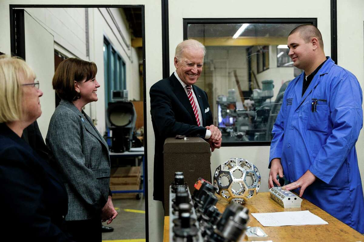 Vice President Joe Biden, center, is given a look inside some of the work going on inside Renton Technical College by RTC instructor and graduate, Adam Polhman, right, photographed Thursday, October 9, 2014, in Renton, Washington. The funding given to RTC was part of the Trade Adjustment Assistance Community College and Career Training competitive grant program, which awarded more than $450 million to 270 community colleges across the country. The consortium that includes RTC received 10 million dollars in the latest round of funding.