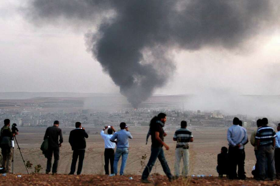 Smoke rises in the Syrian town of Kobani as Turkish Kurds watch near the Mursitpinar border crossing with Syria. Photo: Stringer / Getty Images / 2014 Getty Images